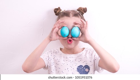 Studio photography: a little girl makes faces with painted Easter eggs. Portrait.