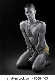 studio photography of a silver bodypainted man in chains while siting on the ground in dark back
