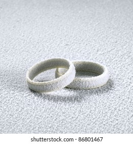 studio photography of two frosted wedding rings in cold ambiance
