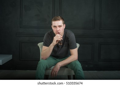 studio photography young brutal guy. man in sunglasses, T-shirt, jeans and high boots on a background of black wall, He is sitting in a white armchair throne.