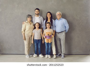 Studio photoshoot group portrait of happy big extended multi generational family. Cheerful mom, dad, grandma, grandpa and two little daughters with toy standing together, looking at camera and smiling