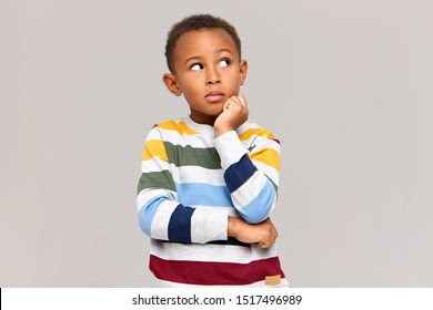 Studio picture of cute dark skinned nine year old boy keeping hand under his chin and looking up with thoughtful pensive facial expression, having curious look, trying to remember something