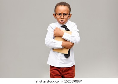 Studio picture of greedy nerdy dark skinned elementary pupil wearing school uniform and eyeglasses holding tight copybook and exclaiming. Childhood, education, learning and lifestyle concept