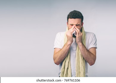 studio picture from a young man with handkerchief. Sick guy isolated has runny nose. man makes a cure for the common cold.Nerd is wearing glasses.