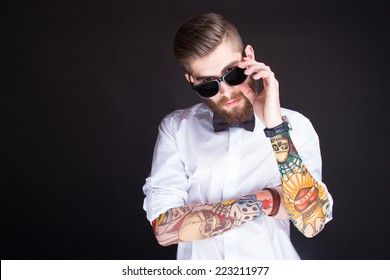 studio portarit of  ayoung fashionable hipster man in white shirt posing over a black background
