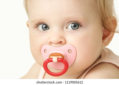 Studio portrait of adorable baby girl with pacifier