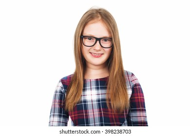 Studio portrait of adorable little girl of 8-9 years old, wearing eyeglasses, standing against white background