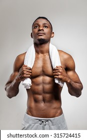 Studio portrait of african american muscular man after sports training with white towel