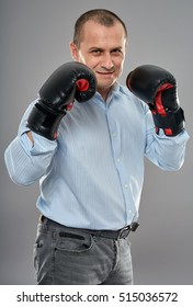 Studio portrait of an aggressive businessman with boxing gloves punching
