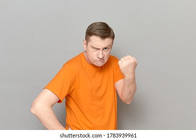 Studio portrait of angry disgruntled blond mature man wearing orange T-shirt, shaking fist in threatening gesture, making rebuke or reprimand, being ready to punch, standing over gray background