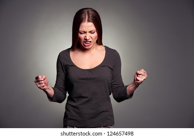 studio portrait of angry young woman over dark background