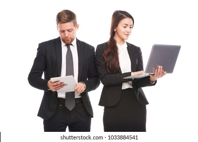 Studio portrait of Asian businesswoman and Caucasian businessman holding laptop and tablet computer