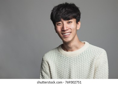 A studio portrait of an Asian man looking ahead with a confident smile