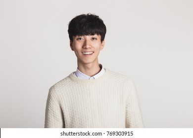 A studio portrait of an Asian young man looking for a camera with confident smiles