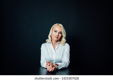 Studio portrait of an attractive blond business woman in a white shirt and black pants against plain background
