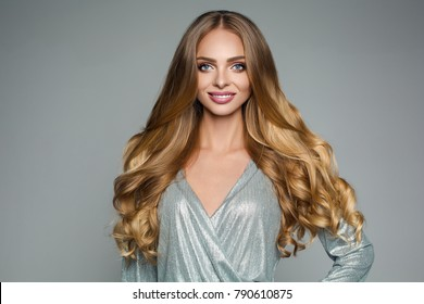 Studio portrait of attractive blonde woman with long thick hair and professional make-up wearing elegant silver blouse smiling at camera over grey background. Isolate. Beauty concept.