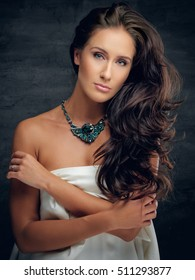 Studio portrait of attractive brunette female with crossed arms in white underwear with green costly necklace.