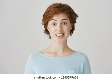 Studio portrait of attractive caucasian female with red hair and freckles feeling awkward, lifting eyebrows and smiling nervously, having no clue what to say in strange situation on meeting