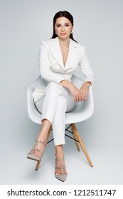 Studio portrait of attractive caucasian woman with dark hair in white suit sitting on chair on plain white background, vertical. Bossy female, job interview concept, confident independent lady