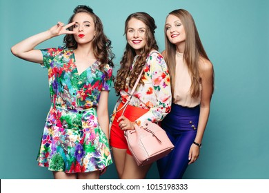 Studio portrait of attractive elegant ladies in summer outlooks posing over blue background. Brunette girl in flowered dress showing peace sign.