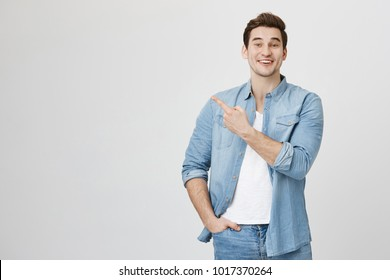 Studio portrait of attractive european man in denim glothes, pointing at upper left corner with index finger, expressing excitement, happiness and surprise, over gray background.