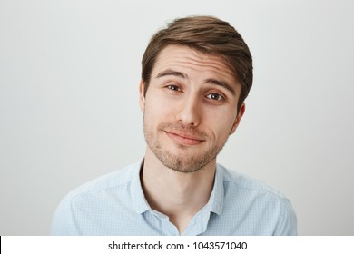 Studio portrait of attractive pleasant male office worker with tired expression, feeling sorry for his coworker who got in trouble, listening her story and nodding, smiling over gray wall