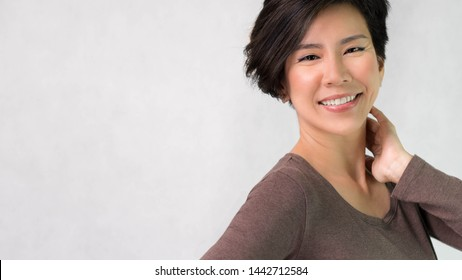 Studio portrait of an attractive smart asian middle aged woman model in her 40s smiling feeling cheerful, Satisfied and Confident. Short hair, Aging, Middle aged beauty and healthy concept. Banner.
