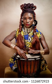 Studio portrait of an attractive young African woman wearing traditional clothing and jewery playing a drum against a brown background