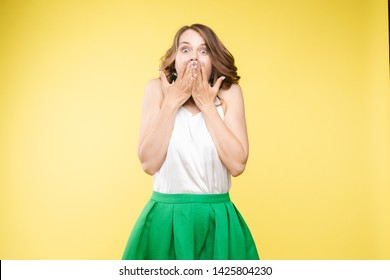 Studio portrait of attractive young caucasian brunette in casual outlook covering her mouth in shock or astonishment. She is shocked, stupified or surprised. Looking at camera with shocked  on yellow