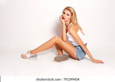 Studio portrait of attractive young girl sitting against white background wearing jeans