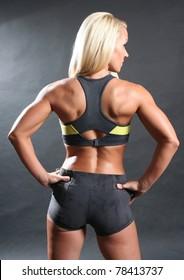 Studio portrait of back side of professional female fitness model.