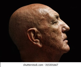 studio portrait of a bald old man