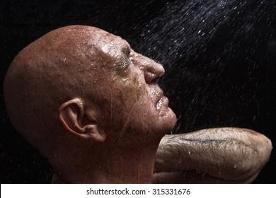 studio portrait of a bald old man showering