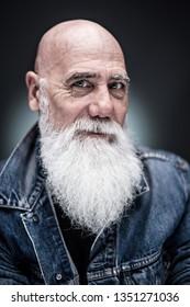 studio portrait of bald senior hipster wearing a long white beard
