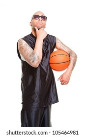 Studio portrait of basketball player wearing black sunglasses standing and holding ball isolated on white. Tattoos on his arms.