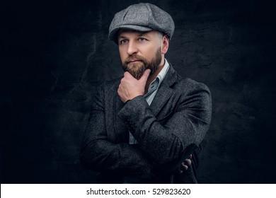 Studio portrait of bearded Englishman in woolen hunting jacket and tweed cap.