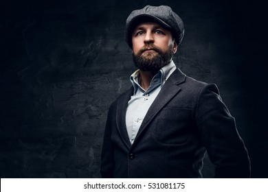 Studio portrait of bearded Englishman in woolen hunting jacket and tweed cap.