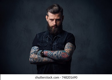 Studio portrait of bearded hipster male with tattoos on his arms