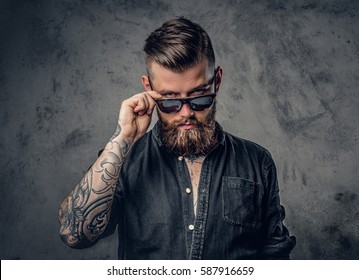 Studio portrait of a bearded hipster man with tattoos on his arms and neck  dressed in a black shirt and sunglasses