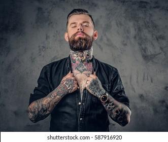 Portrait de studio d'un hipster barbu avec des tatouages sur les bras, la poitrine et le cou.