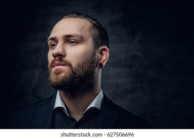 Studio portrait of bearded male dressed in a blue jacket over grey vignette background.