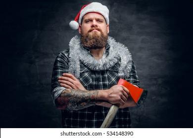 Studio portrait of bearded male in Santa's hat holds the axe.