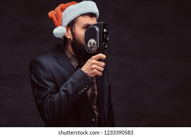 Studio portrait of bearded man wearing a classic suit and santa hat holding a retro camera, making a photo.