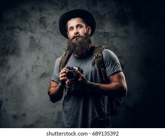 Studio portrait of bearded tattooed photographer holds compact camera over grey background.