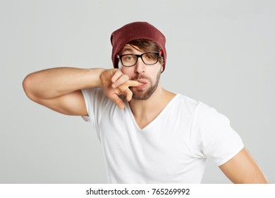 Studio portrait of a bearded young man posing on grey background sucking his finger fun funny face expressive comic youth fooling around hipster beard concept.