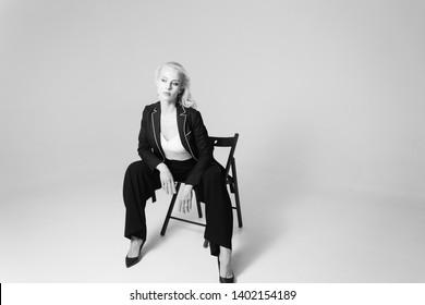 Studio portrait of beautiful blond woman in a black dress against white plain background