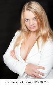 Studio portrait of beautiful blond woman in white blazer in front of black background