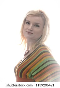Studio portrait of a beautiful blonde girl. She is dressed in a knitted blouse in a strip, on her neck she has a beautiful necklace. Clothing in the style of the 1970s. A clean white background