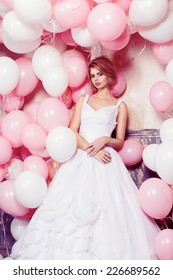 Studio portrait of beautiful blonde girl in white wedding dress with oink and white balloons