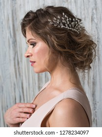 Studio portrait of beautiful bride with makeup and hairstyle decorated by rhinestone shiny hair accessory